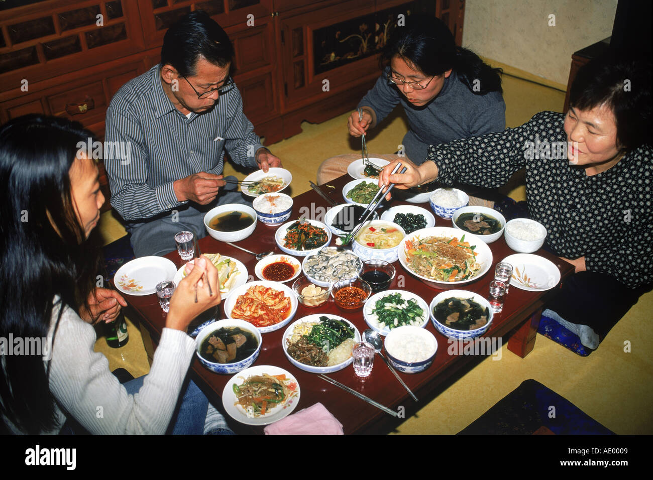 Family sitting at dinner table eating variety of home made Korean foods in South Korea Stock Photo