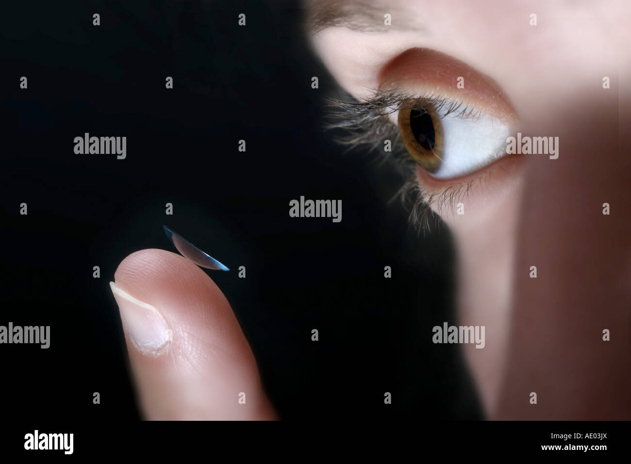 woman putting in contact lenses - Stock Image