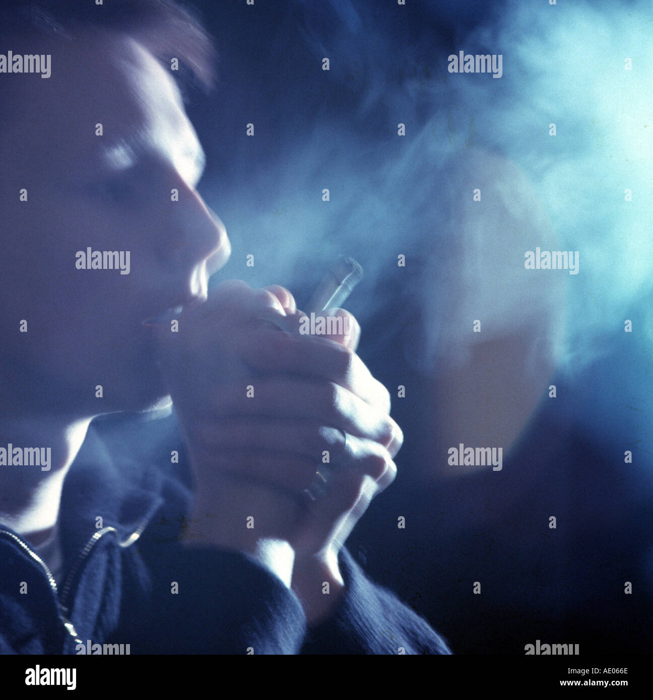young man smokin a joint - Stock Image
