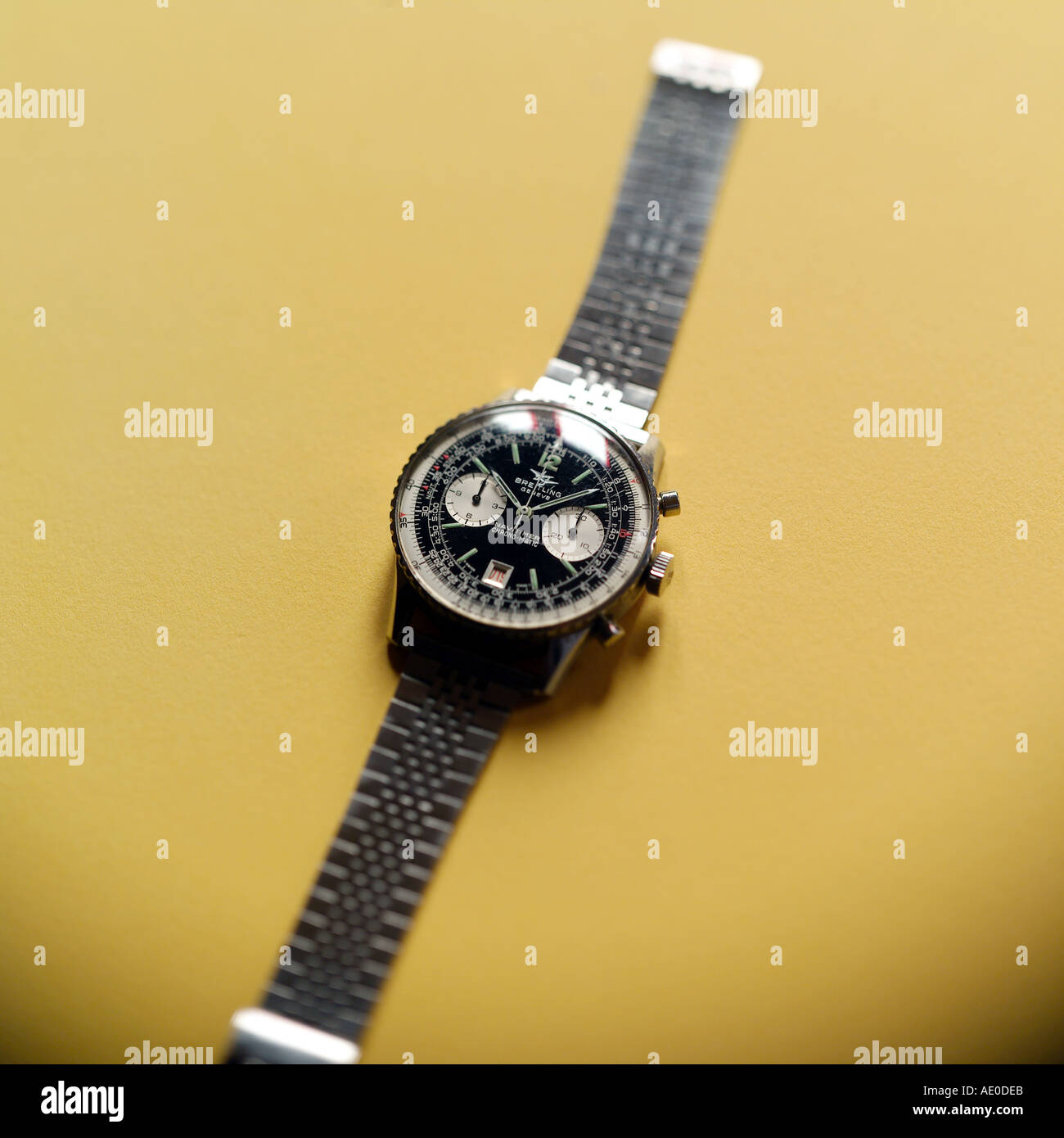 BREITLING SWISS CHRONOGRAPH WRIST WATCH WITH SELECTIVE FOCUS ON YELLOW BACKGROUND - Stock Image
