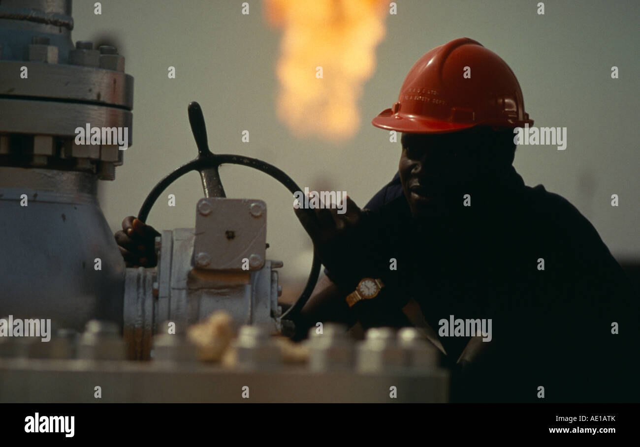 NIGERIA West Africa Oil Industry worker with flare of burnt off gas behind him - Stock Image
