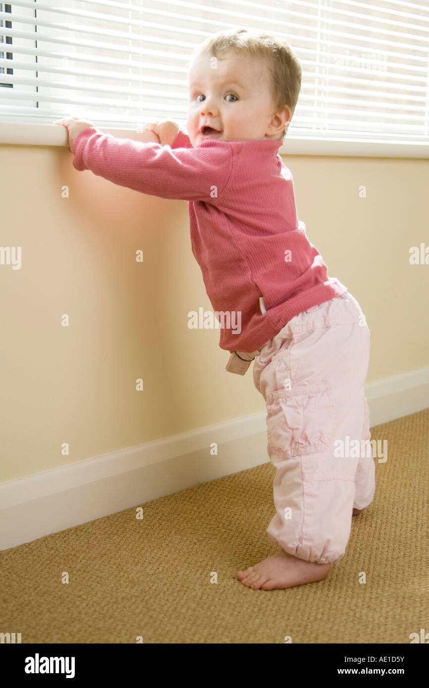 a toddler learning to walk - Stock Image