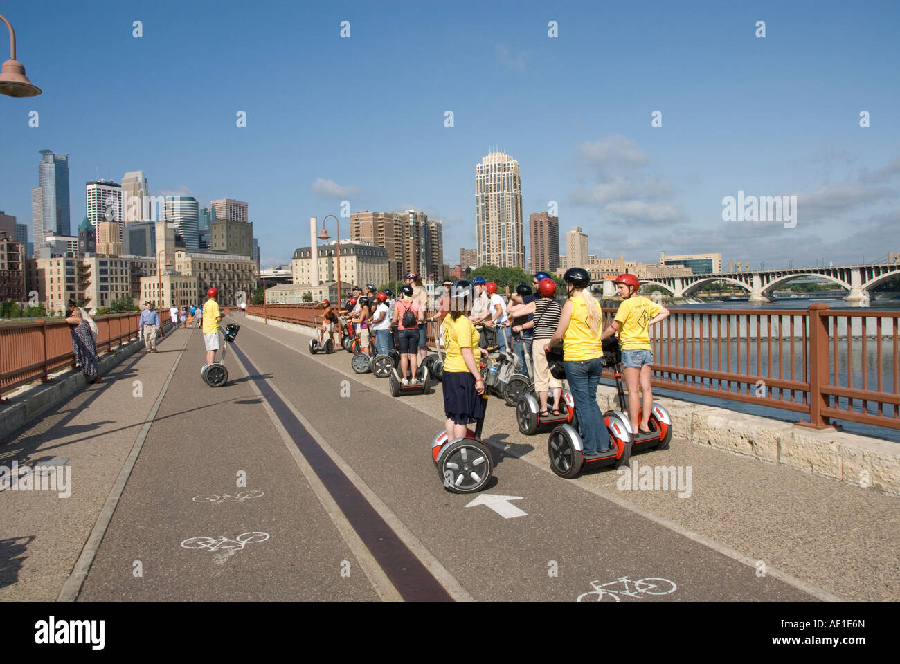 Segway riders Minnesota Twin Cities Minneapolis Saint Paul Stone Arch Bridge crosses Mississippi Minneapolis MN - Stock Image
