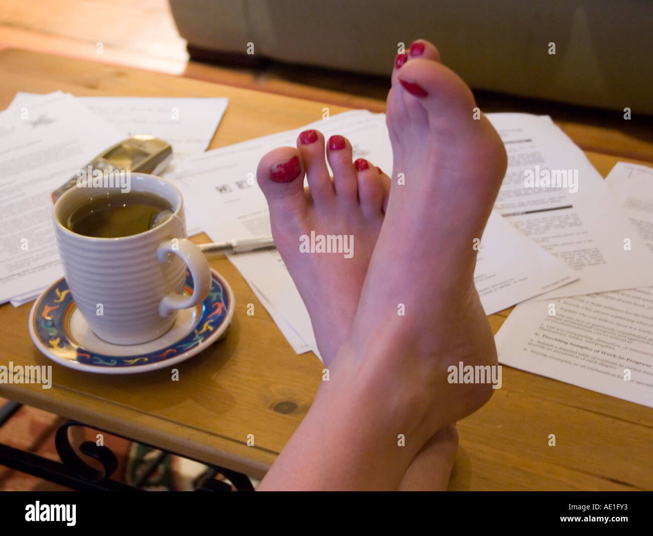 https://c8.alamy.com/comp/AE1FY3/feet-with-red-painted-toe-nails-on-coffee-table-with-cup-papers-and-AE1FY3.jpg