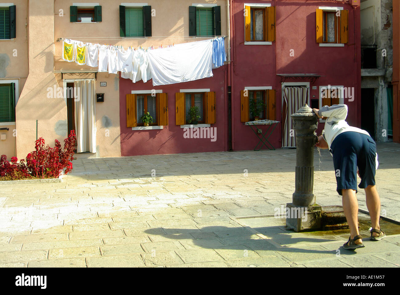 A line of laundry against coloured houses man drinking from water tap - Stock Image