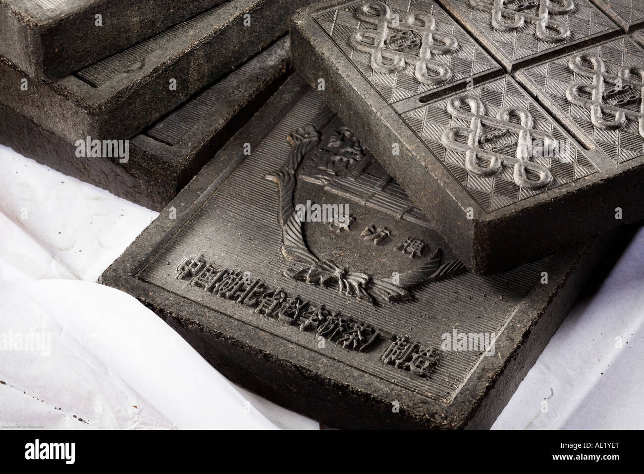 Richly embossed tea bricks stacked atop one another. - Stock Image