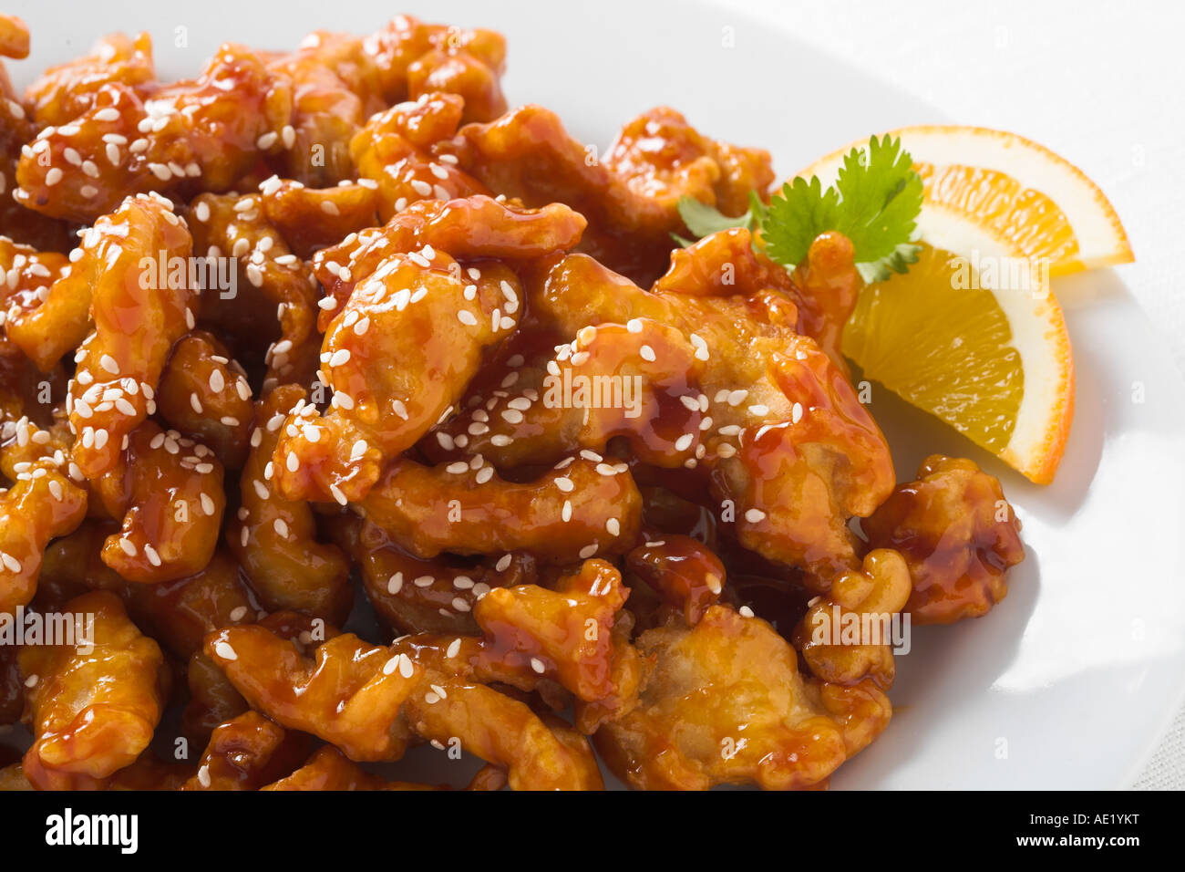 Orange Sesame chicken peel chinese food with seeds seed dish white plate delicious mouth watering savory savor eat - Stock Image