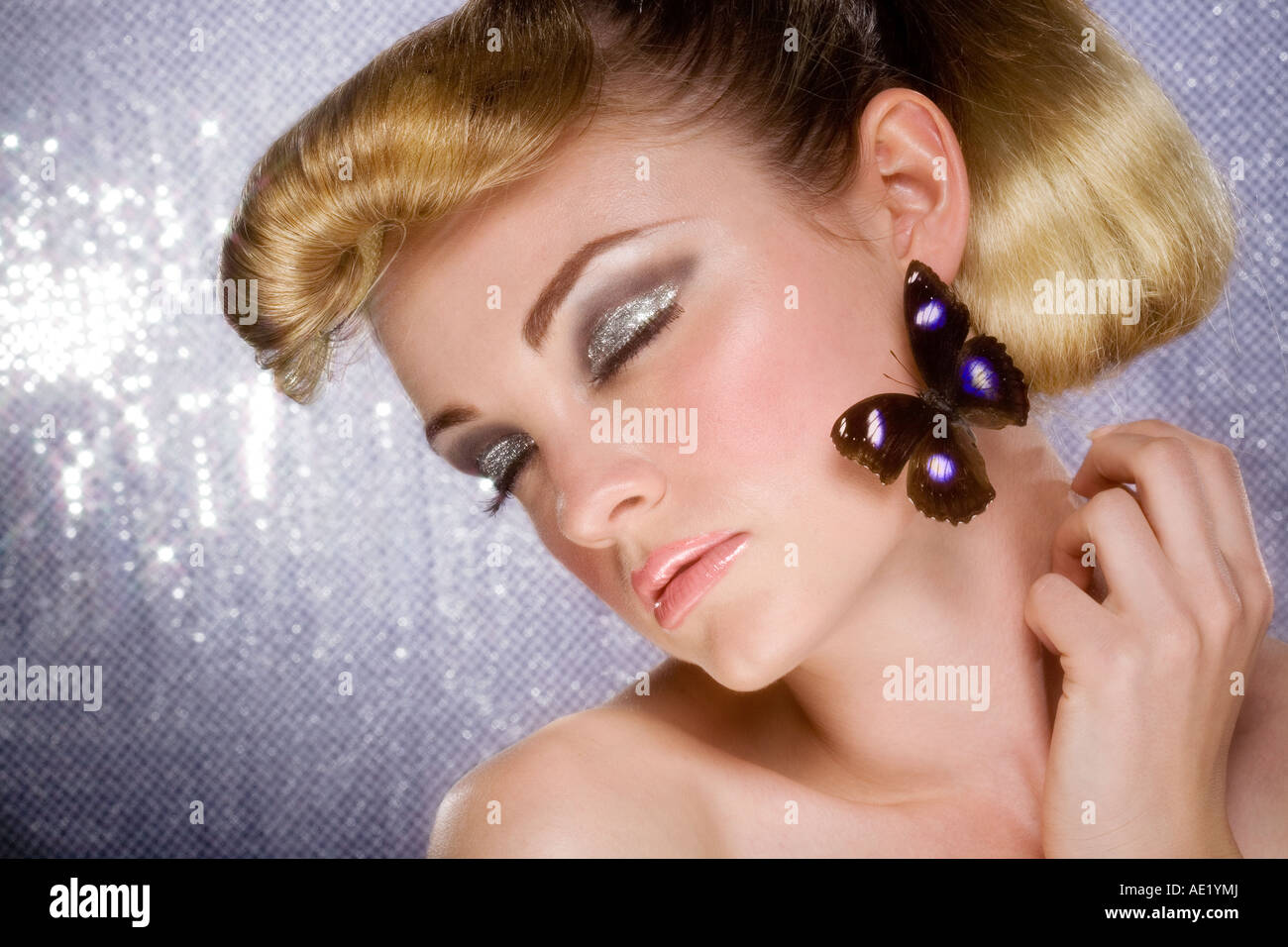 A portrait beautiful, glamorous young girl with a butterfly on her face. - Stock Image