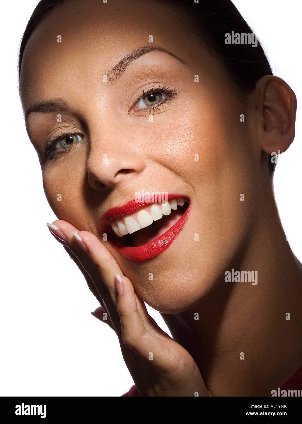 A young woman smiling with her hand up to her cheek. Stock Photo