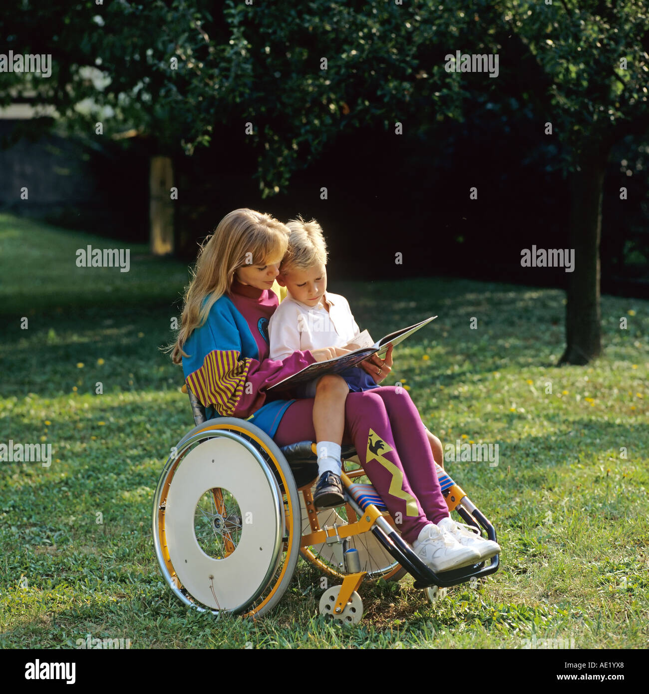 Disabled woman in wheelchair reading book to little boy in garden - Stock Image
