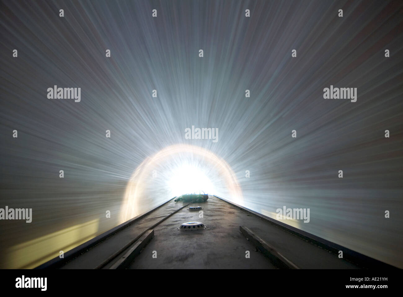 Navigating through a canal tunnel on a narrowboat picture taken with a slow shutter speed to give a motion effect - Stock Image