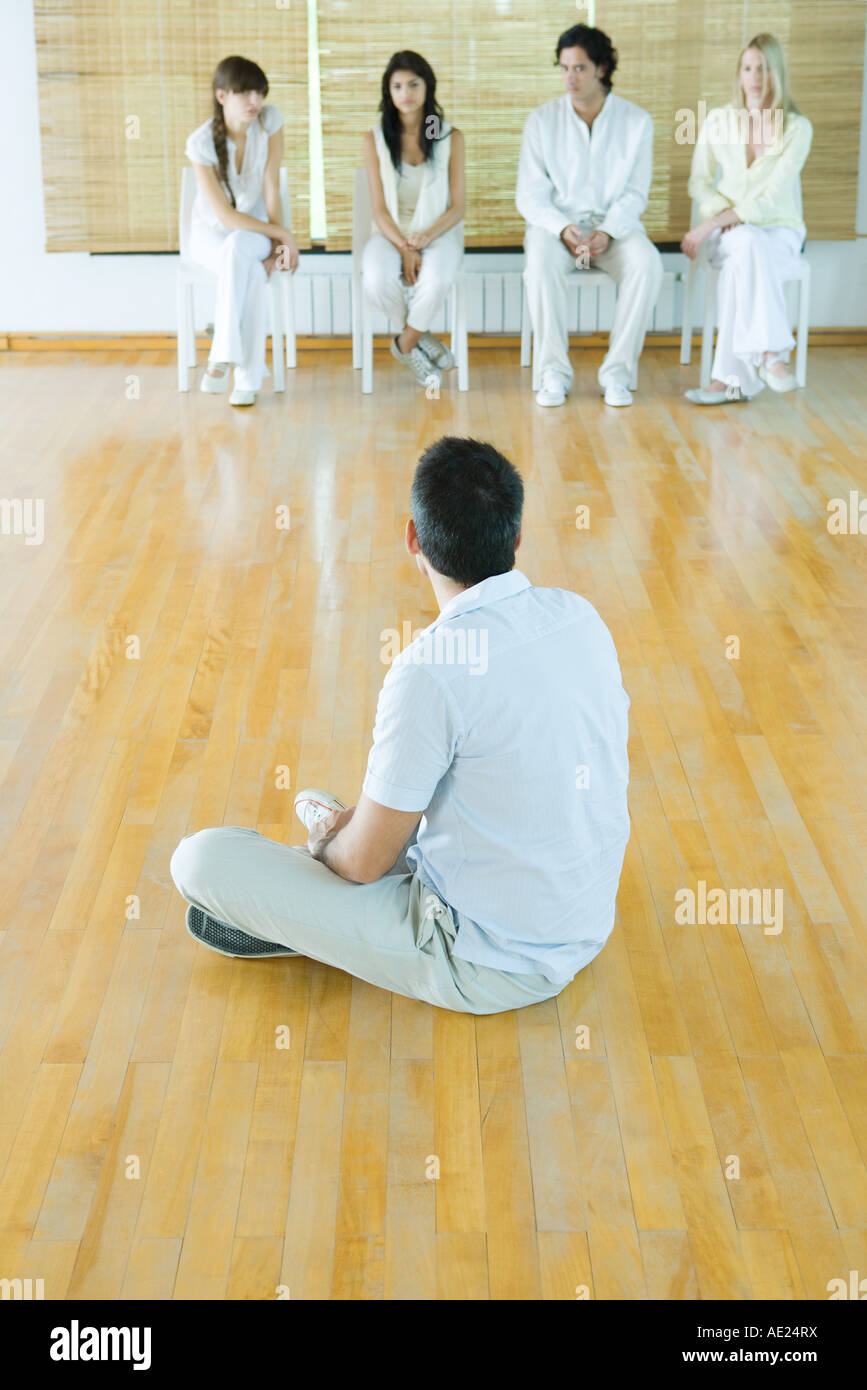 Group therapy, man sitting on floor facing four adults sitting in chairs - Stock Image