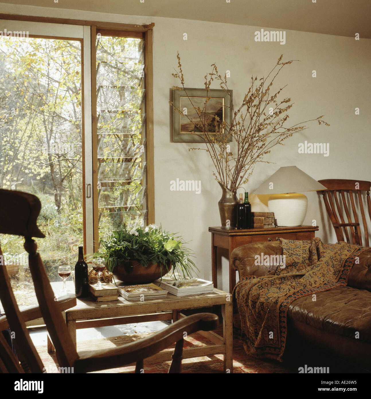 Houseplants in bowl on simple wooden table in front of sliding glass door in country living room with old brown leather sofa