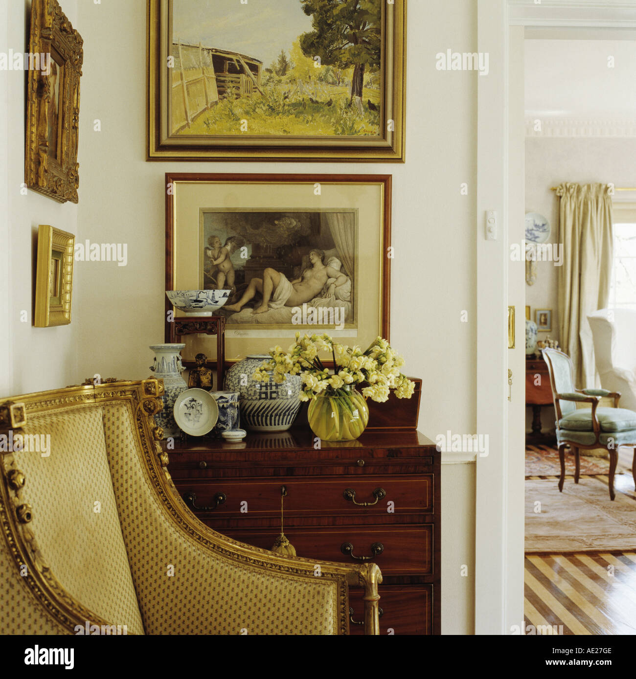 Pictures On Wall Above Antique Chest Of Drawers Beside Gold Armchair In  Corner Of Living Room