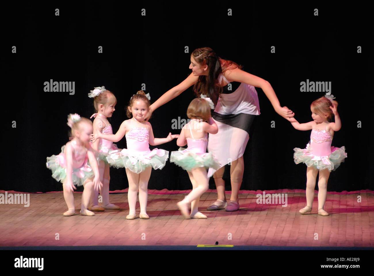 Girls perform on stage during a dance recital - Stock Image