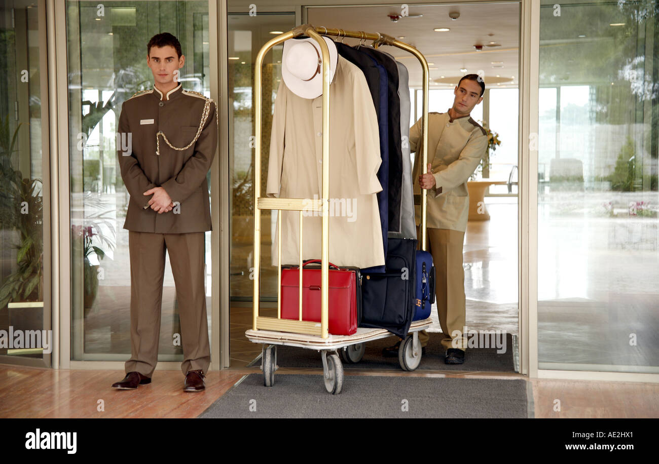 Bellboy delivering luggage to hotel with doorman standing by - Stock Image