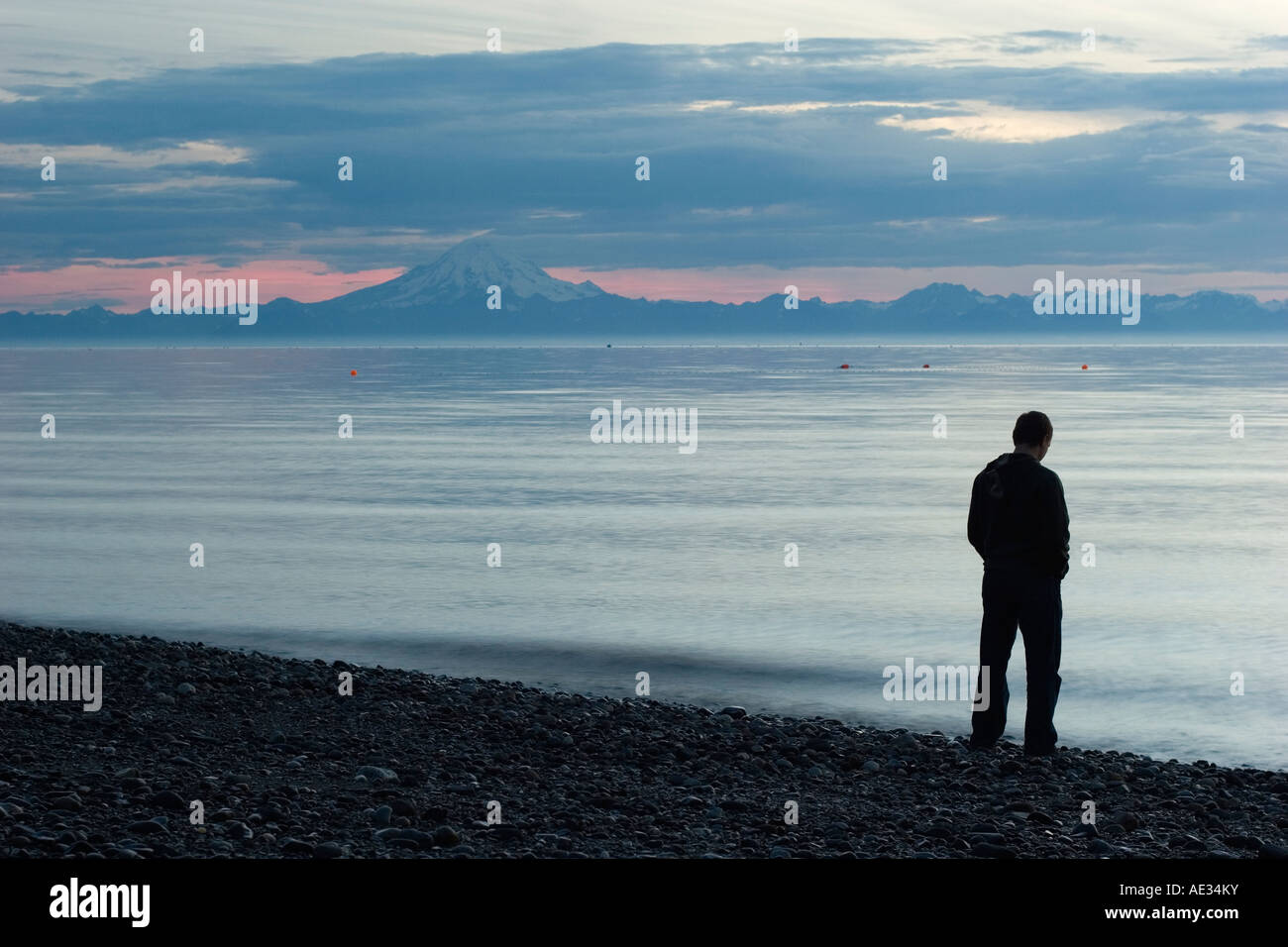 A beach of Cook Inlet, Alaska, sunset time with a silhouette of a guy standing next to the water Stock Photo