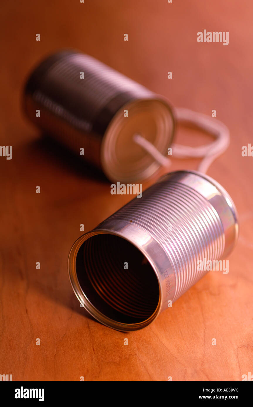 Tin can telephone on wooden table - Stock Image