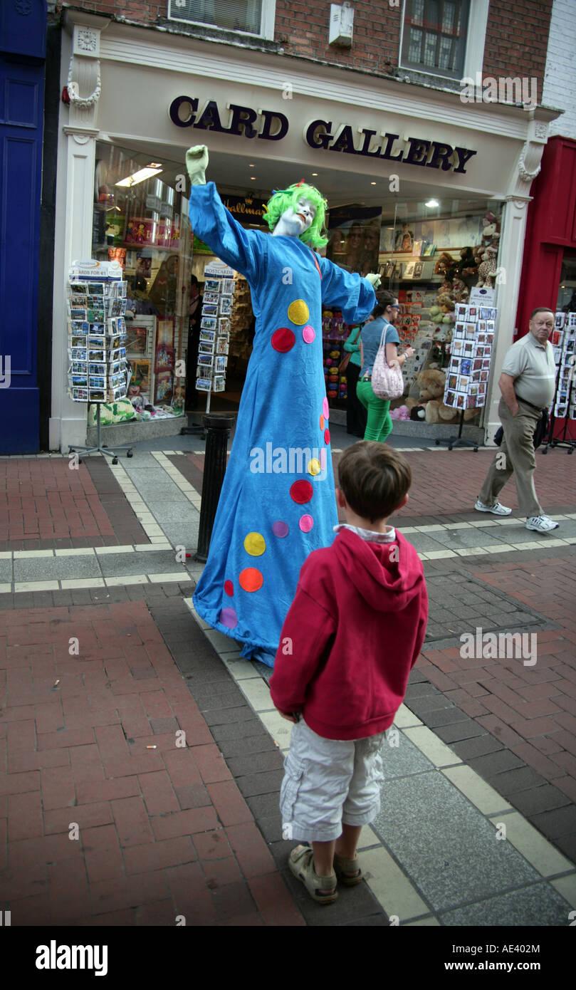 small boy entranced by lady street entertainer Grafton Street Dublin - Stock Image