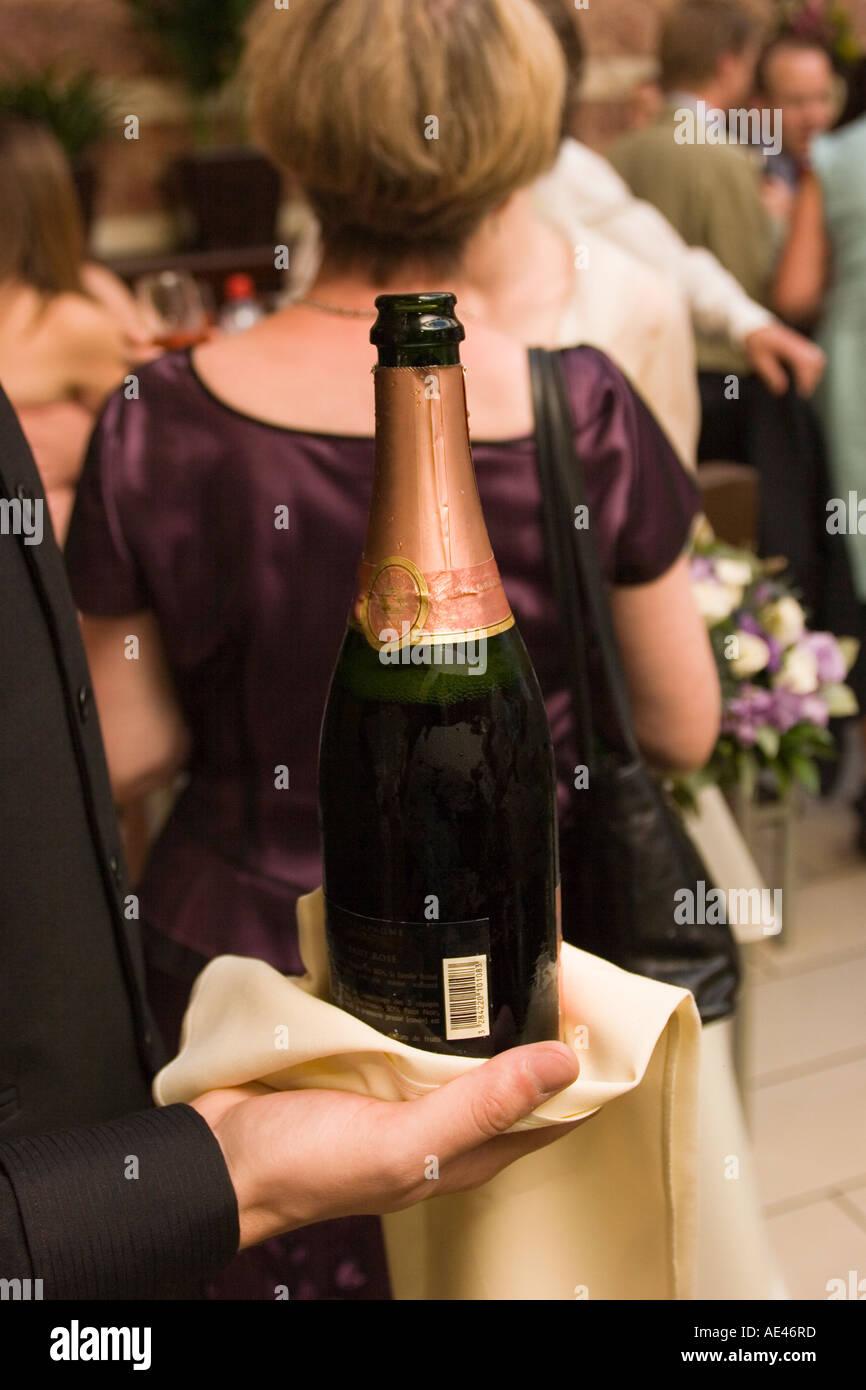 weddings waiter holding bottle of pink champagne Stock Photo