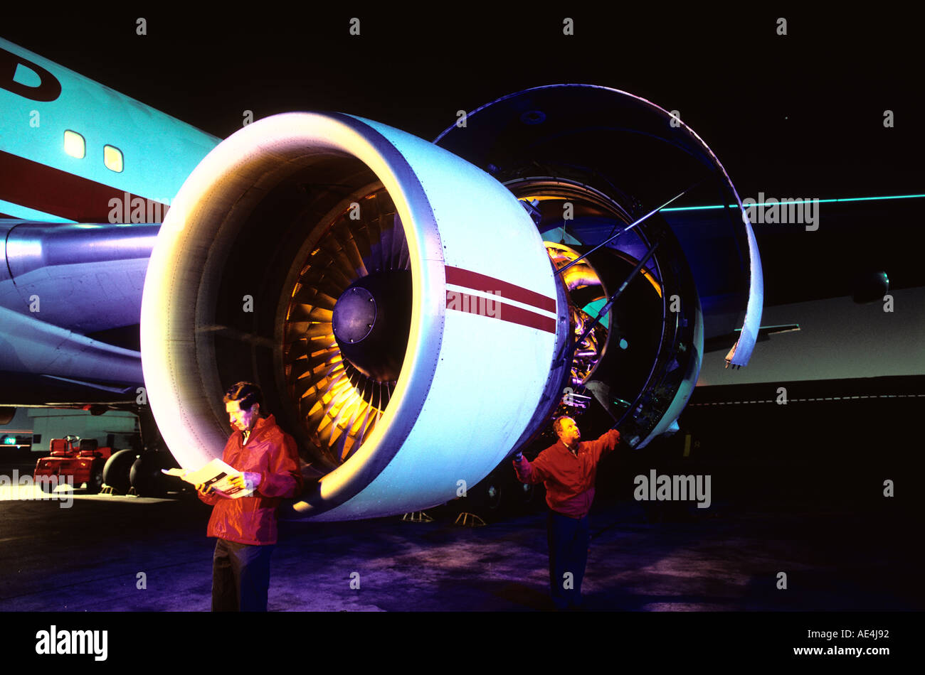 mechanics working on commercial airliner jet engine at night - Stock Image