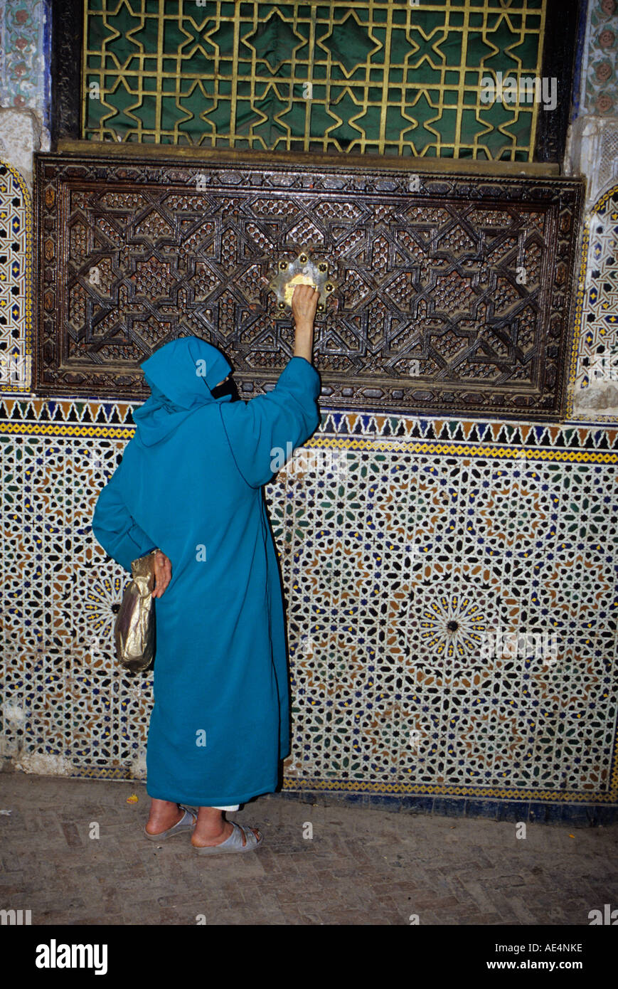 Fez, Morocco. Almsgiving. A woman places a coin in the alms box at the Zawiya of Moulay Idris II in Old Fez. Stock Photo