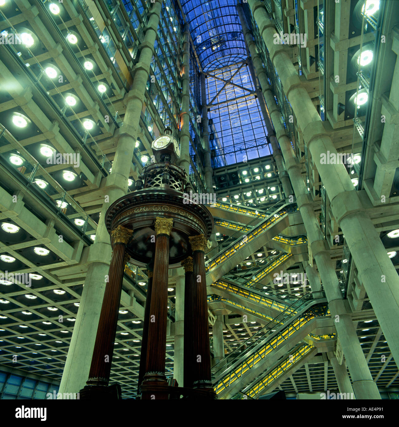 Dramatic view up atrium interior of Lloyd s of London building Richard Rogers Partnership Architects showing floors escalator and Lutine Bell City of London EC3 England - Stock Image