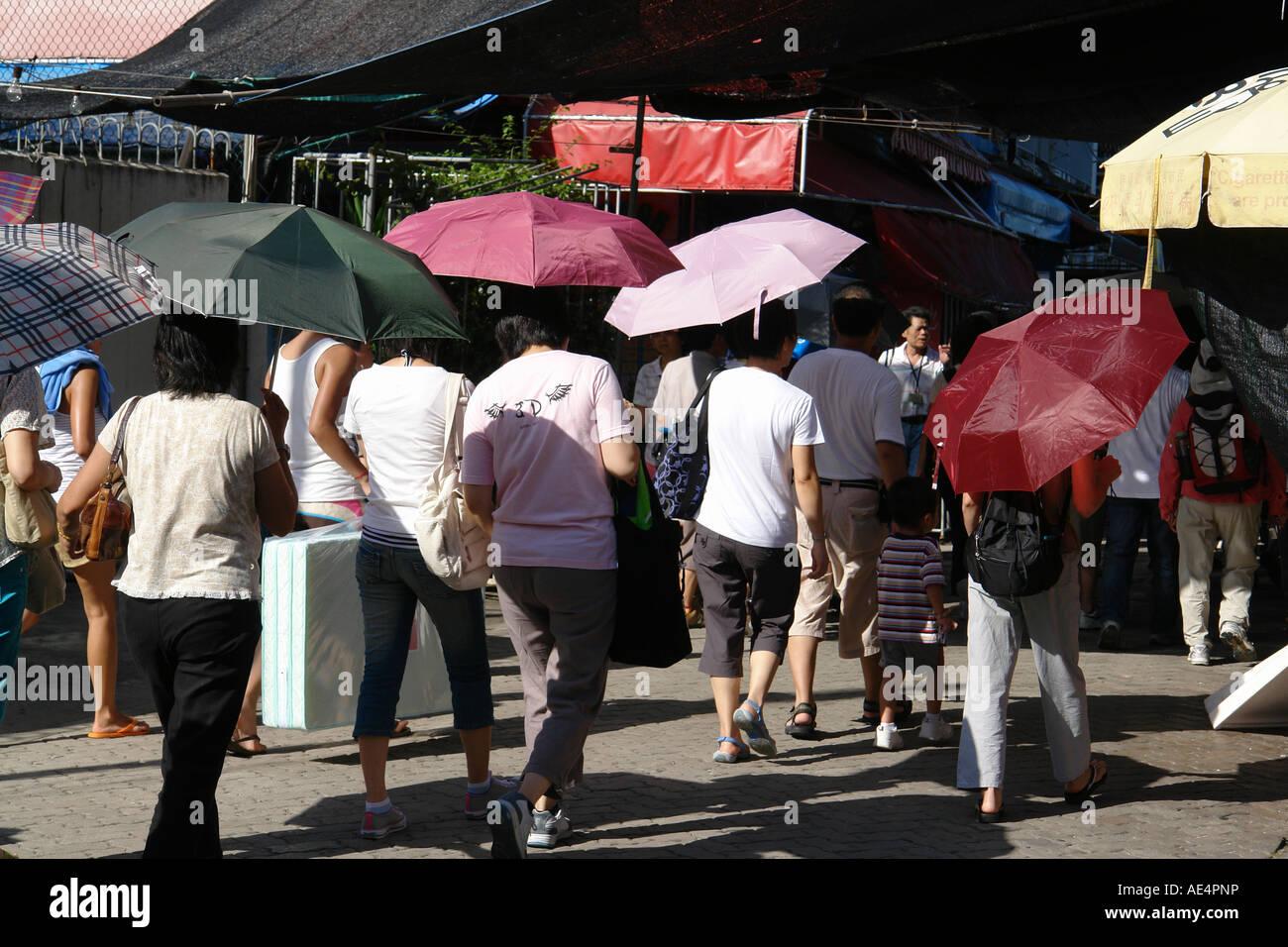 People with UV protection umbrella Cheung Chau Hong Kong China - Stock Image