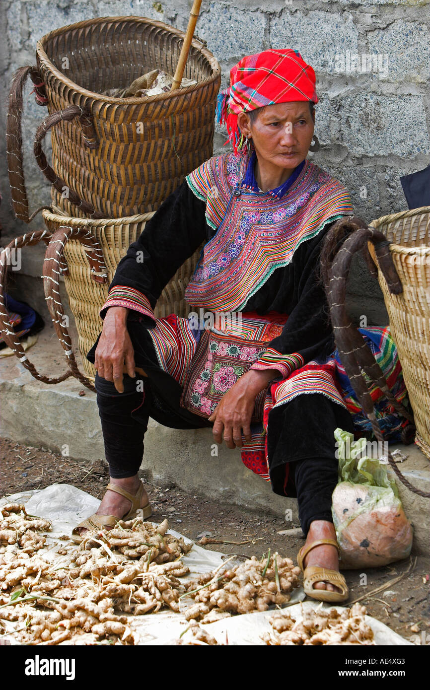 Woman selling root vegetables Bac Ha hilltribe market known for colourful Flower Hmong traders north Vietnam Stock Photo