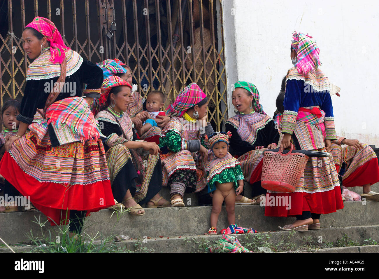 Young mothers and children on steps Bac Ha hilltribe market known for colourful Flower Hmong traders north Vietnam Stock Photo