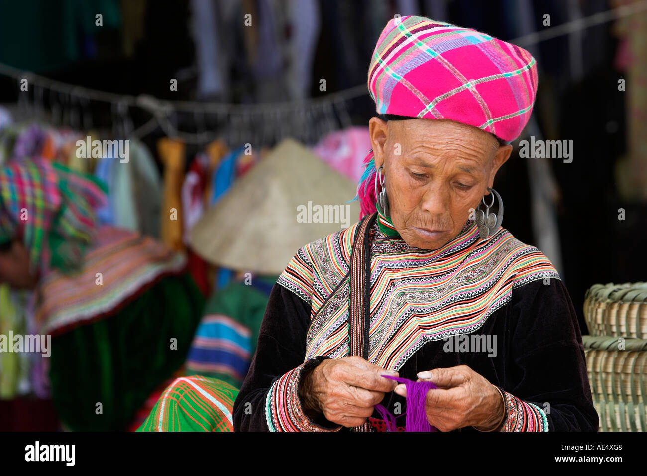 Old woman sorts coloured yarn Bac Ha hilltribe market known for colourful Flower Hmong traders north Vietnam Stock Photo
