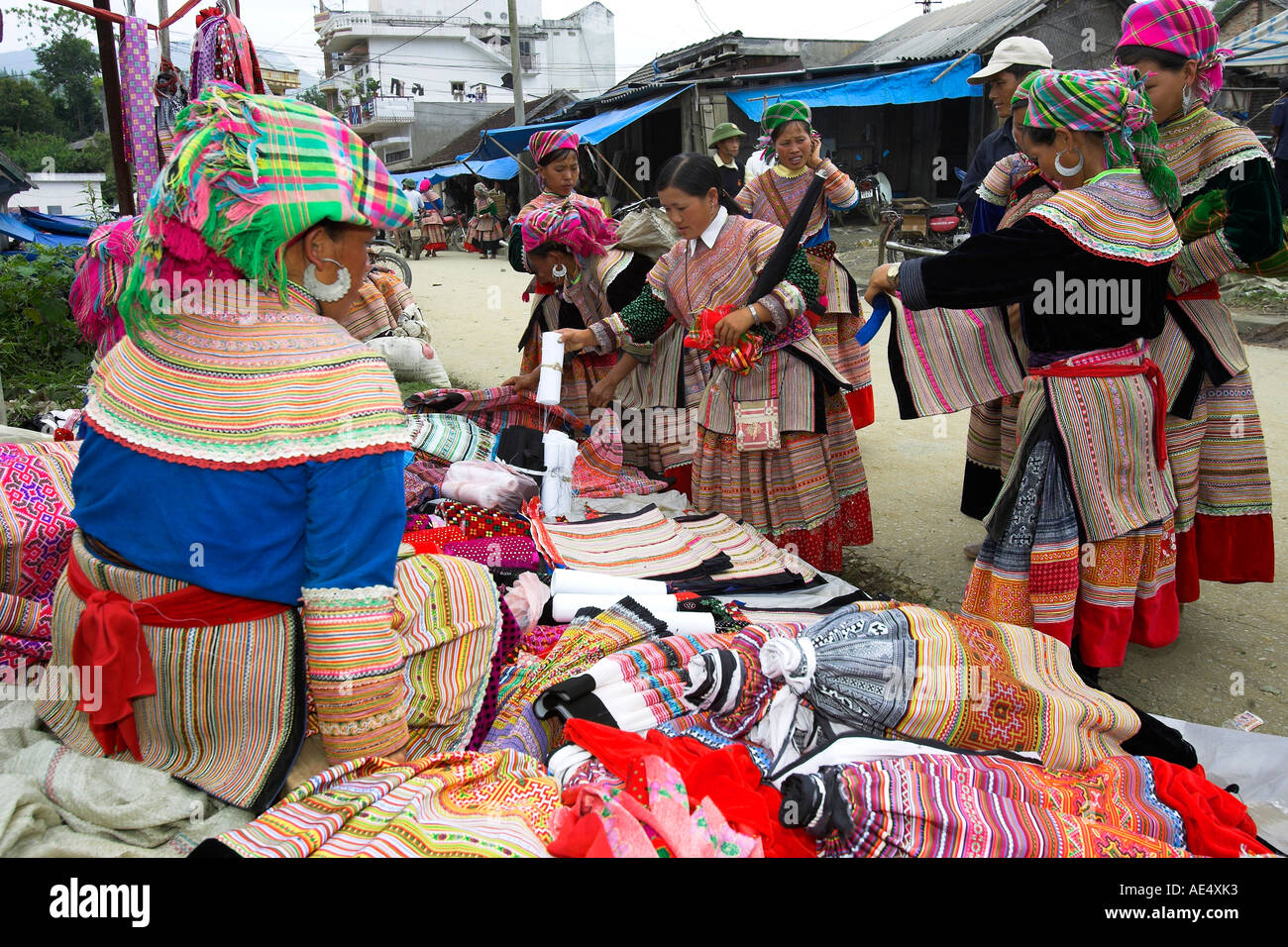 Young women inspect clothing and fabrics Bac Ha hilltribe market known for colourful Flower Hmong traders north Stock Photo