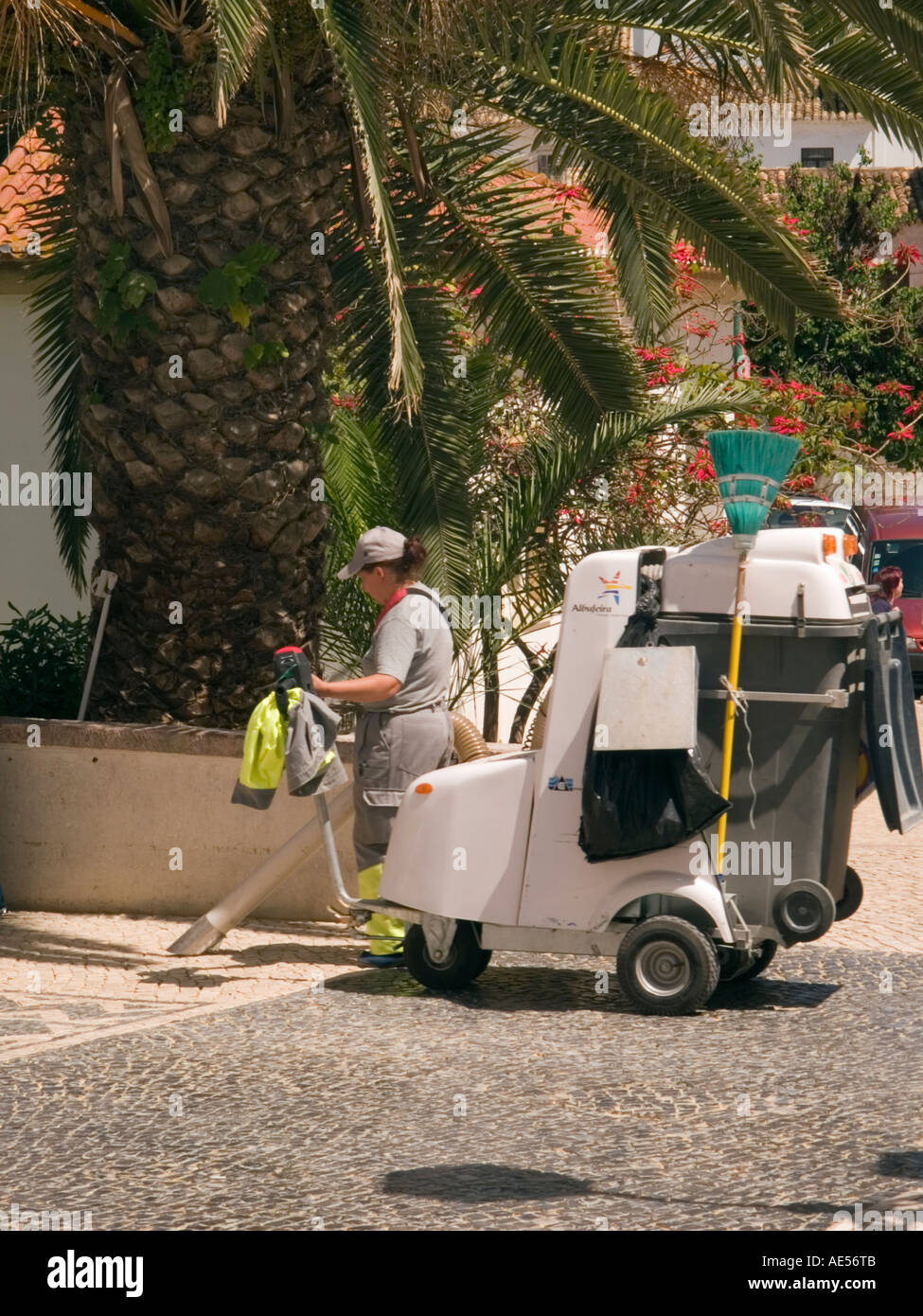 LADY STREET CLEANER with machine for vacuuming and collecting rubbish. - Stock Image