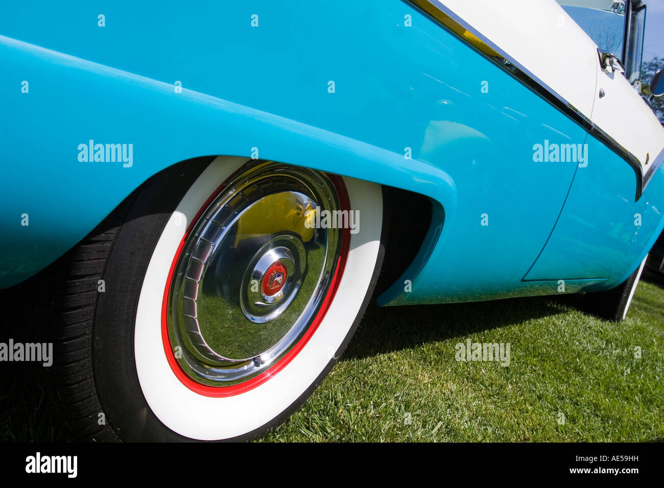 Side of a turquoise and white 1955 Ford Fairlane convertible classic car with red rim on whitewall tire and side - Stock Image