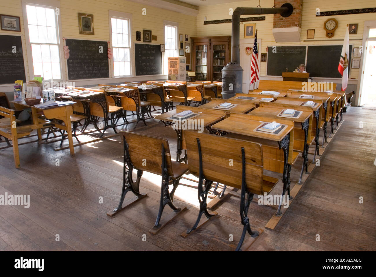 Classroom in replica of 1800s era one room schoolhouse with childrens desks chalkboards and wood stove Old Town - Stock Image