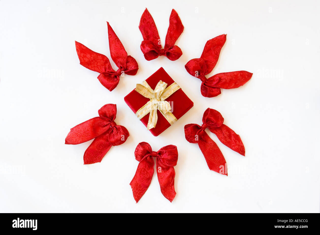 Christmas present wrapped in red velvet with gold ribbon and bow surrounded by circle of six red bows - Stock Image