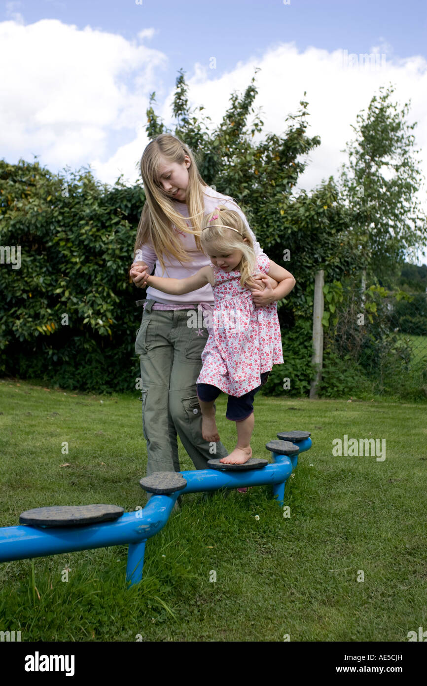 Elder sister young blonde teenager helps younger niece walk across obstacle course in in playground UK - Stock Image
