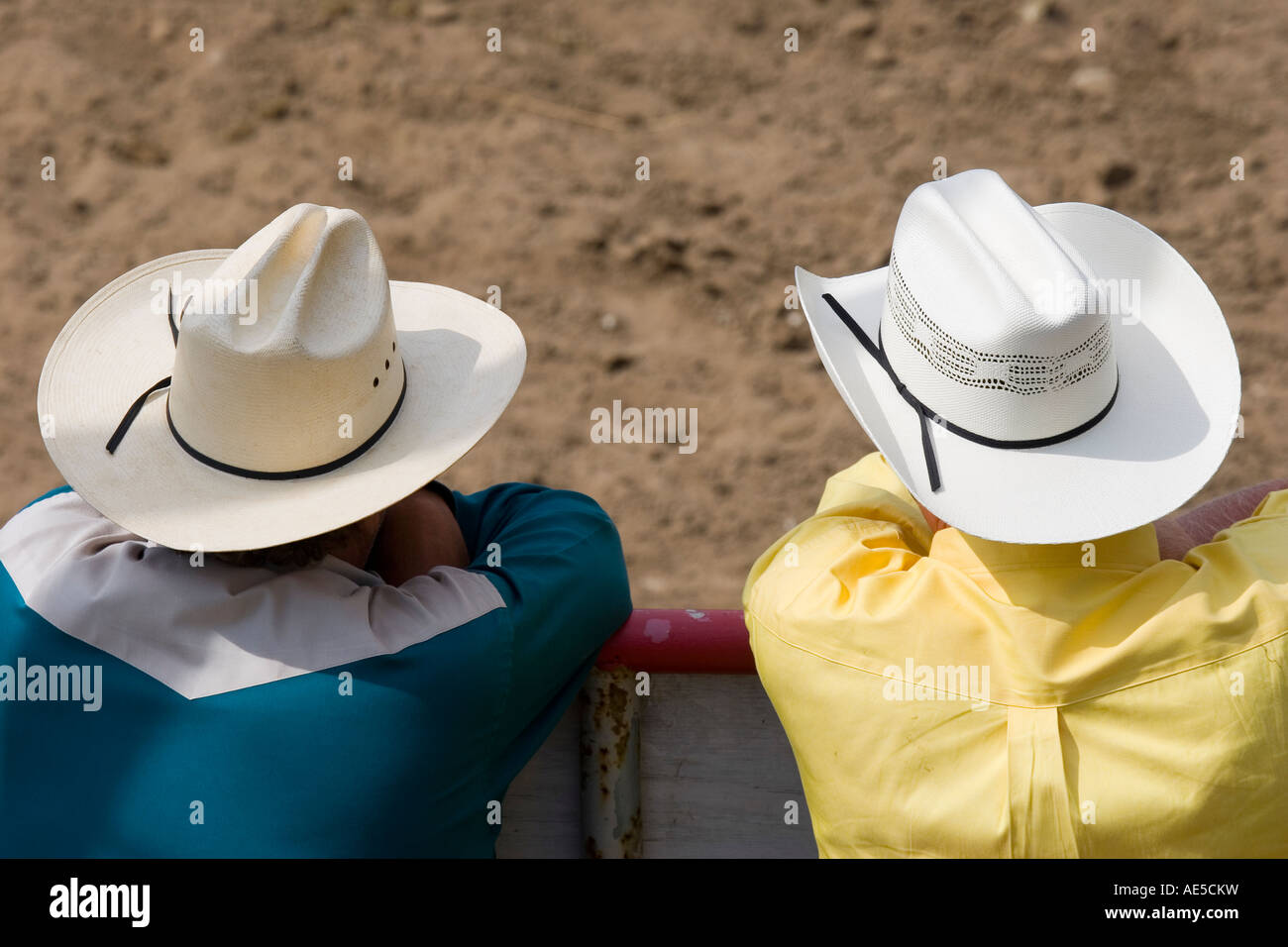a1126d57f Two men in white straw cowboy hats watching the events at a rodeo ...