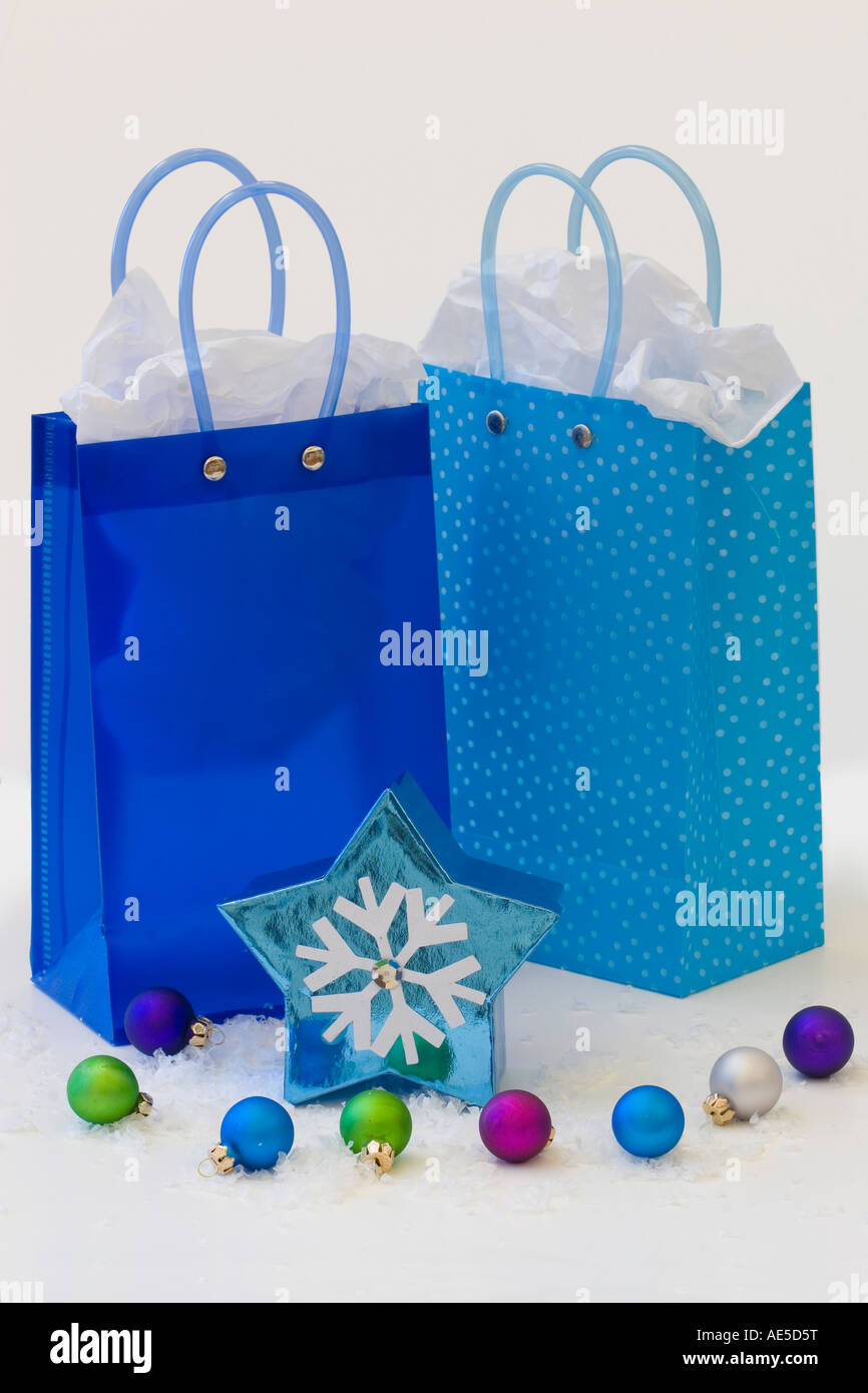 Three blue gift bags with tissue paper and snowflake star shaped box winter holiday gifts for Christmas or Hanukkah - Stock Image