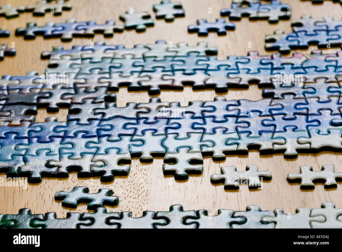 Pieces of jigsaw puzzle being put together on a table - Stock Image