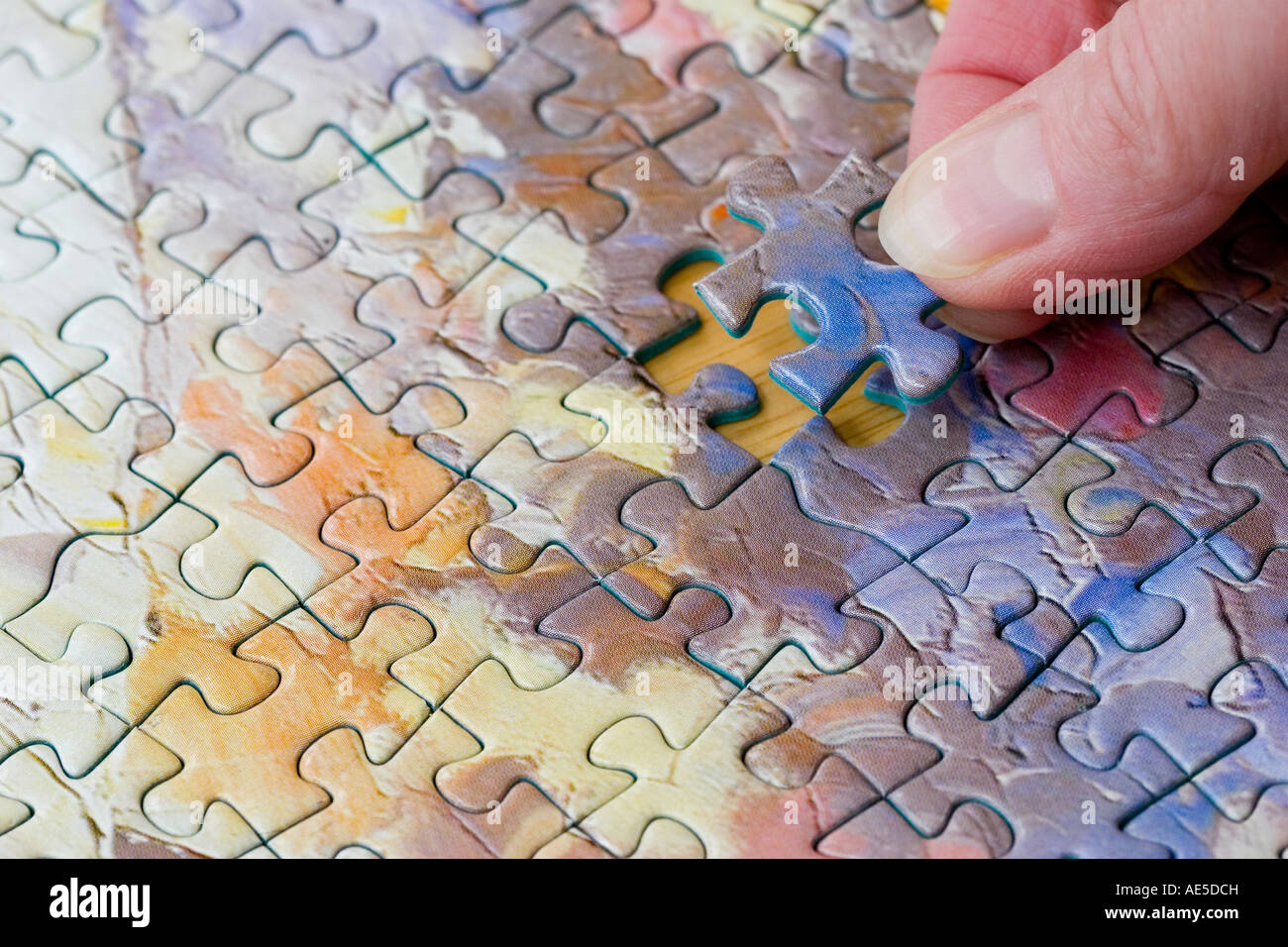 Jigsaw Puzzle Pieces Connected Together With Hand Putting In The Last Missing Piece