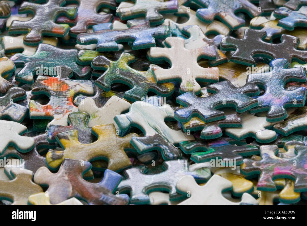 Closeup of the pieces of a jigsaw puzzle in a pile conveys idea of confusion or trying to figure out a problem - Stock Image