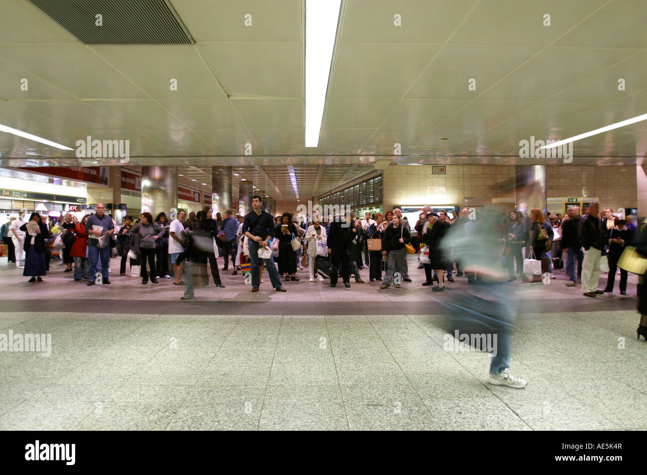 people standing in waiting area of penn station looking up at train