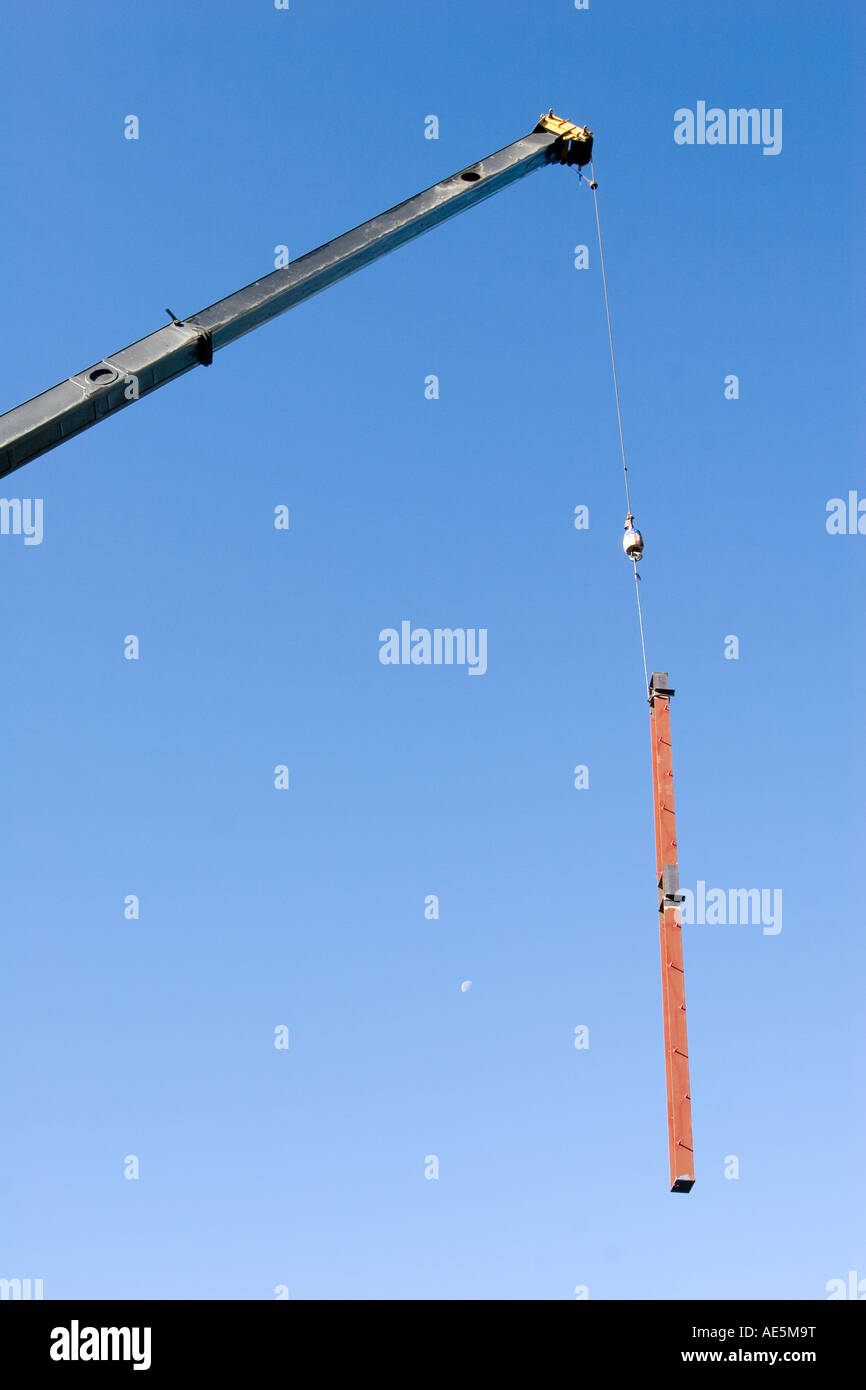 Arm of a crane extended and lowering steel beam from hook with the moon in the sky at a construction site - Stock Image