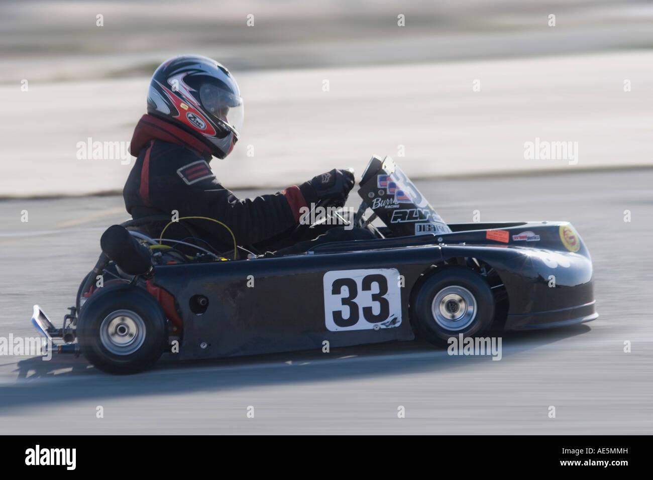 Go kart racer in kart number 33 whizzing by on an asphalt track - Stock Image