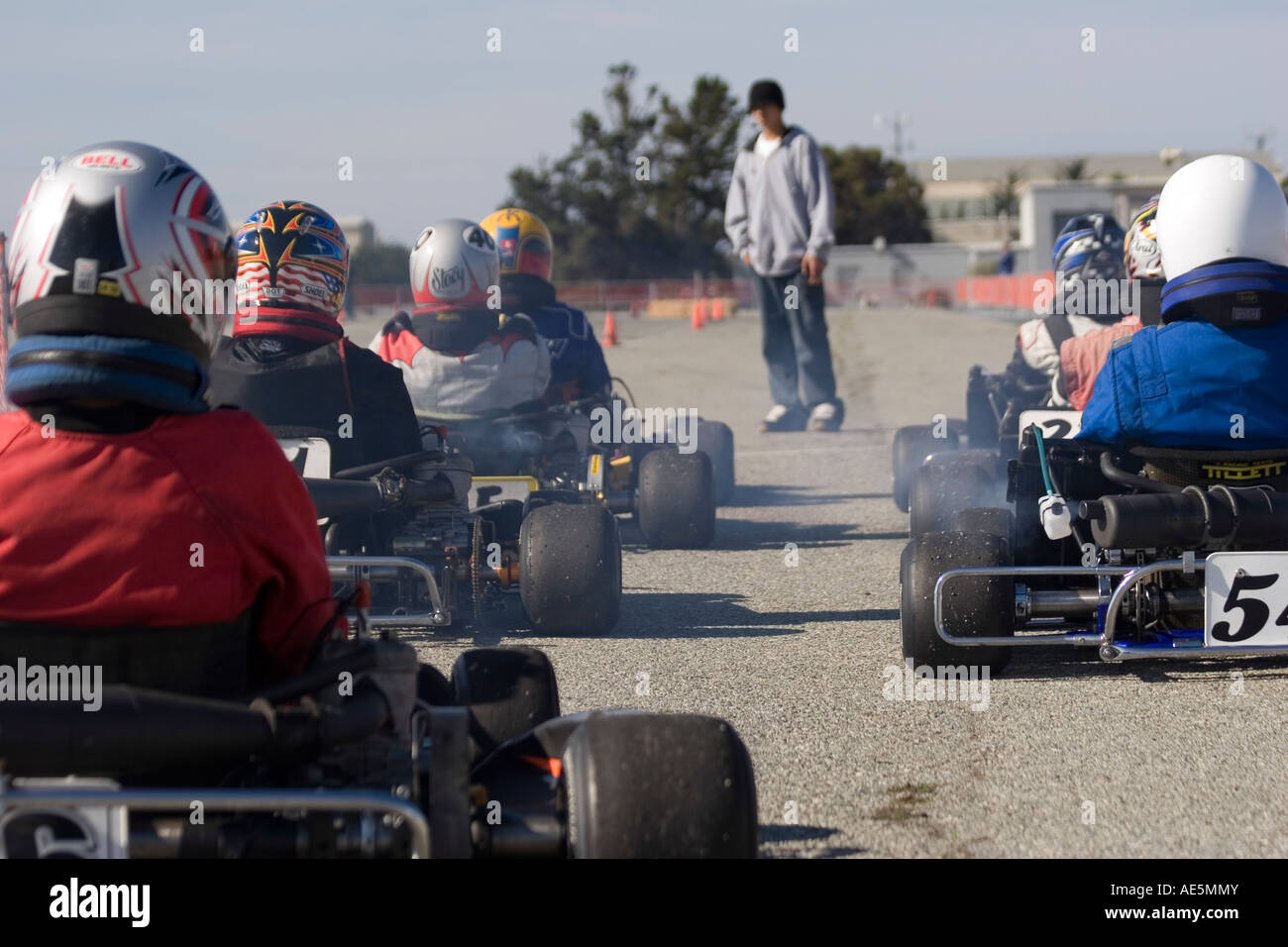 Go kart racers lined up with their engines running loudly at the starting line of a race on asphalt - Stock Image