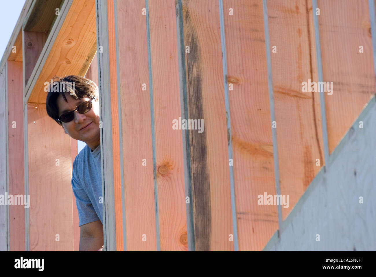 Man looking through a window in a wood framed wall at a residential construction site - Stock Image
