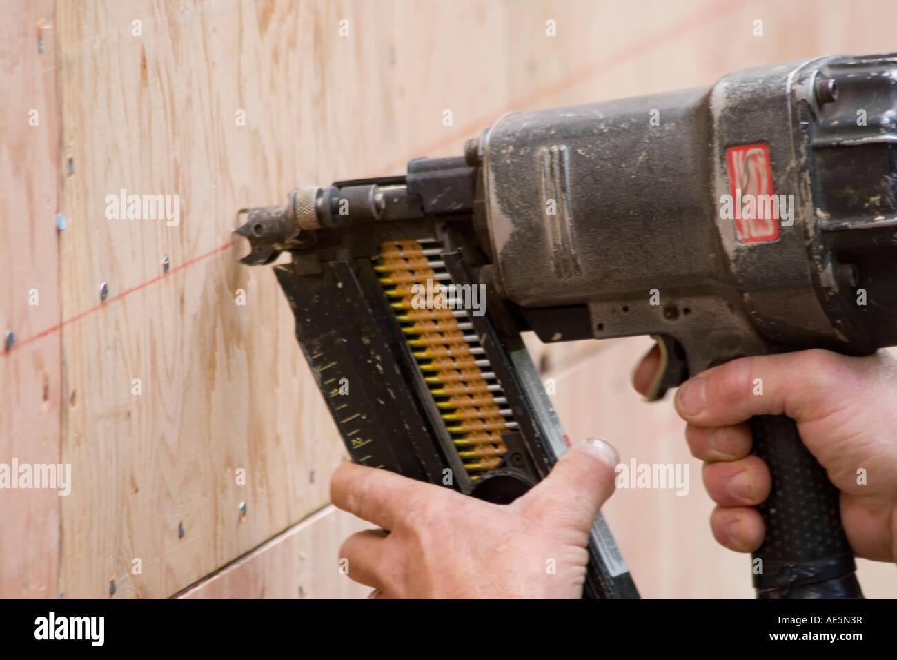 Carpenter Using Nail Gun To Shoot Nails Into Plywood