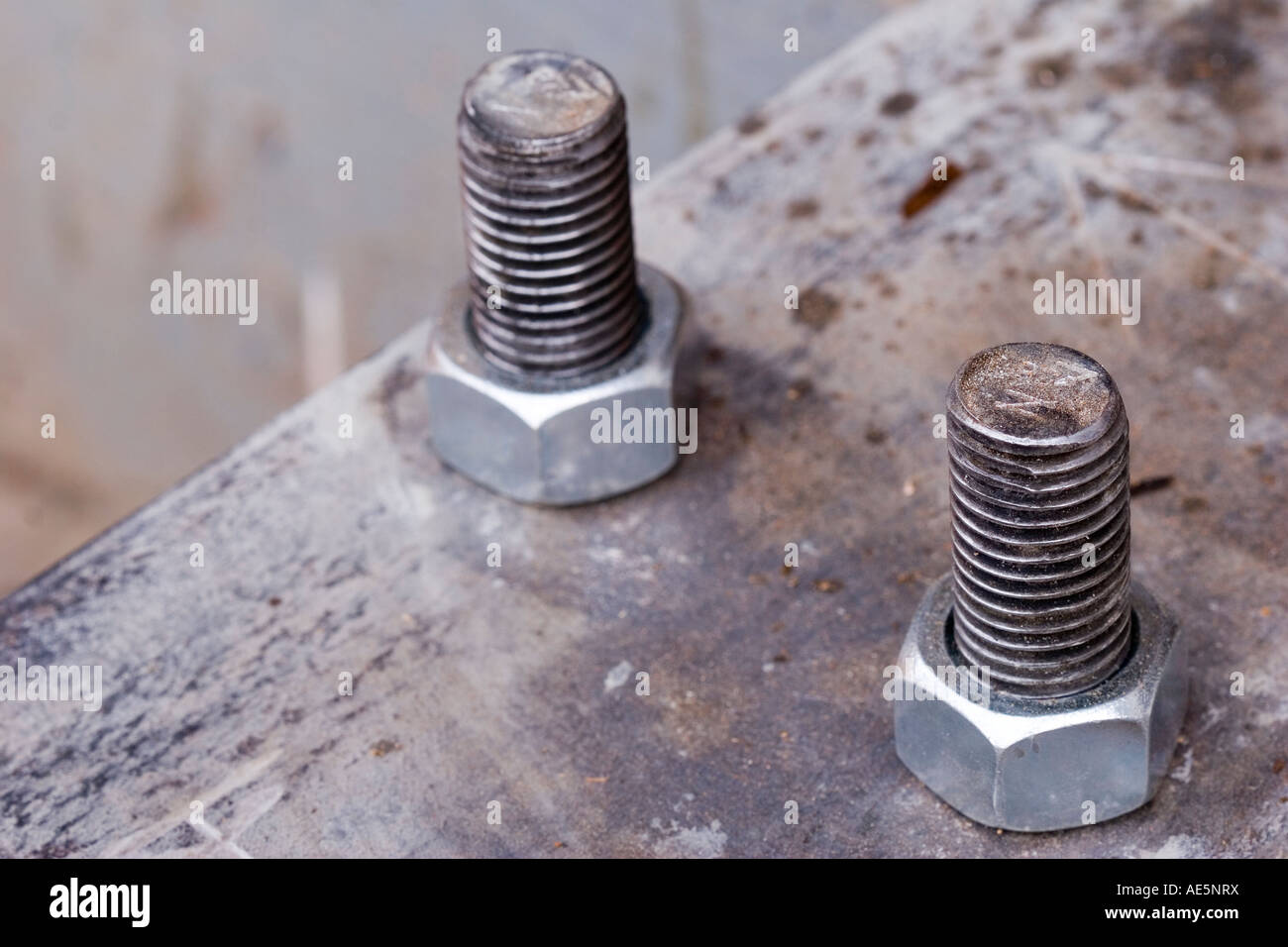 Two galvanized steel bolts secured to rusty metal plate with nuts Stock Photo