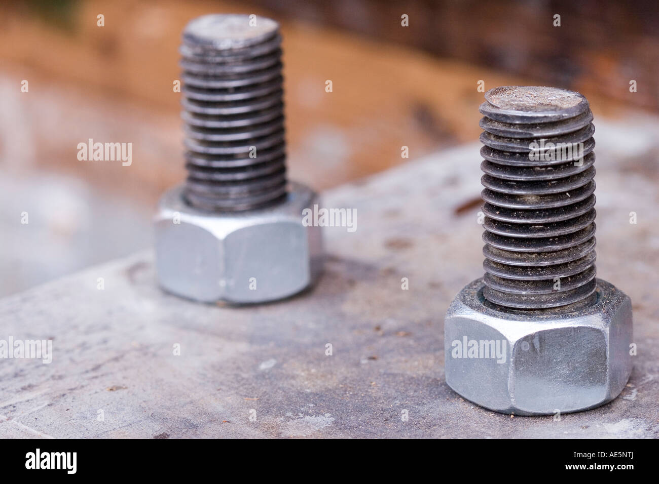 Two galvanized steel bolts with nuts secured to rusty metal plate - Stock Image